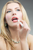 Blonde doing makeup with makeup stick Royalty Free Stock Photos