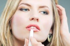 Blonde doing makeup with makeup stick Royalty Free Stock Photography