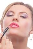 Blonde doing makeup with makeup stick Stock Image