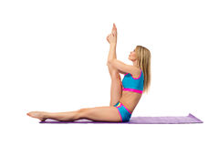 Blonde doing stretching exercise on training mat Royalty Free Stock Images