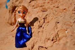 Blonde Dolls are playing in sand and walking together in a rocky area royalty free stock photos