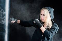 Blonde in dozen doende vrouw in zwarte ponsenzak Stock Foto