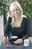 Blonde drinking coffee. Beautiful blond girl drinking coffee at cafe royalty free stock images