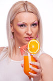 Blonde drinking orange juice Royalty Free Stock Images