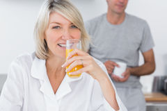 Blonde drinking orange juice in kitchen Royalty Free Stock Photos