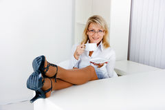 Blonde is drinking tea in the workplace Stock Photography