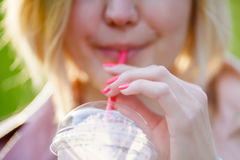 Blonde drinks cocktail from tube Royalty Free Stock Photo