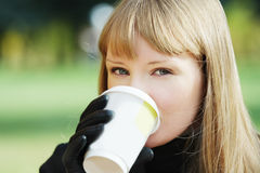 Blonde drinks outdoors. Young blonde woman in black overcoat drinks outdoors from paper cup Royalty Free Stock Image