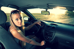 Blonde driver. Young blonde women in the car. Cross process like colors Stock Photos