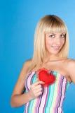 Blonde dulce en un fondo azul con el corazón Fotos de archivo libres de regalías