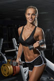Blonde with dumbbells do exersises  in gym Royalty Free Stock Photo