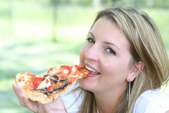Blonde eating pizza slice Stock Image