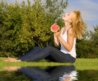 Blonde eats watermelon in the park Royalty Free Stock Photography