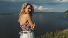Blonde on the edge of the cliff. In a beautiful dressblonde posing on camera on the edge of the cliff in a beautiful dress ,in the background the river stock footage
