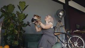 Blonde in een grijze kledingszitting op de laag in een mooie ruimte en het spelen met de hond, werpt zij hem pret, omhelzingen en stock video