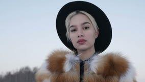 Blonde in een hoed in de winter stock videobeelden