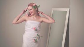 Blonde in een kleding dichtbij een spiegel stock videobeelden