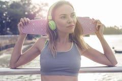 Blonde Eignungsfrau der Junge recht, die hörende Musik der hellgrünen Kopfhörer trägt und rosa Skateboard bei der Stellung auf t  Lizenzfreie Stockbilder