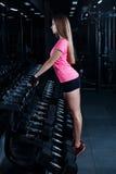 Blonde Eignungsfrau in der Sportkleidung mit dem perfekten Körper, der in der Turnhalle aufwirft Attraktives sportliches Mädchen, Lizenzfreies Stockbild