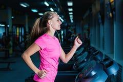 Blonde Eignungsfrau in der Sportkleidung mit dem perfekten Körper, der in der Turnhalle aufwirft Attraktives sportliches Mädchen, Lizenzfreie Stockfotografie