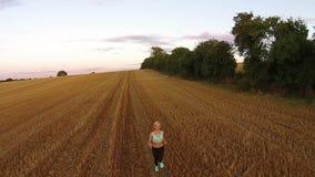Blonde Eignungsfrau, die auf dem Feld läuft stock footage