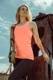 Blonde Eignungsfrau, die mit trx Eignungsbügeln auf Metallrostiger Oberfläche aufwirft Stockfotos