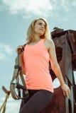 Blonde Eignungsfrau, die mit trx Eignungsbügeln auf Metallrostiger Oberfläche aufwirft Lizenzfreies Stockfoto