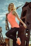 Blonde Eignungsfrau, die mit trx Eignungsbügeln auf Metallrostiger Oberfläche aufwirft Stockbild