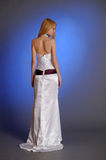 Blonde in an elegant white evening gown stands with his back turned in profile Stock Photos