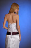 Blonde in an elegant white evening gown stands with his back turned in profile Royalty Free Stock Photography