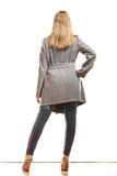 Blonde elegant woman in gray coat rear view. Fashion. Young blonde fashionable woman in elegant gray belt coat. Female model in full body rear view isolated on Stock Photos