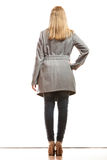 Blonde elegant woman in gray coat rear view. Fashion. Young blonde fashionable woman in elegant gray belt coat. Female model in full body rear view isolated on Royalty Free Stock Photo