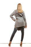 Blonde elegant woman in gray coat rear view. Fashion. Young blonde fashionable woman in elegant gray belt coat. Female model in full body rear view isolated on Royalty Free Stock Images