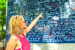 Montmartre I love you wall. Blonde elegant woman pointing popular Mur des Je t`aime. I Love You Wall is a monument landmark in Jehan Rictus garden square near Royalty Free Stock Images