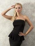 Blonde elegante Frau nahe Modewand Stockbilder