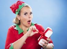 Blonde Elfenfrau, die ein Geschenk öffnet Stockbild