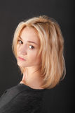 Blonde em um fundo preto Imagem de Stock