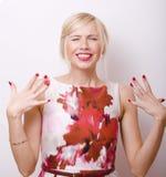 Blonde emotionale Frau mit den roten Lippen und den Nägeln Lizenzfreies Stockfoto