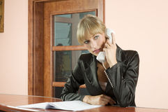 Blonde Empfangsdame am Telefon Stockfotografie