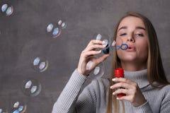 Blonde en burbujas que soplan del cuello alto Cierre para arriba Fondo gris Fotografía de archivo libre de regalías