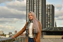 Blonde en capa en el tejado del rascacielos imagen de archivo libre de regalías