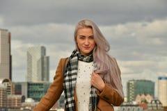 Blonde en capa en el tejado del rascacielos imágenes de archivo libres de regalías