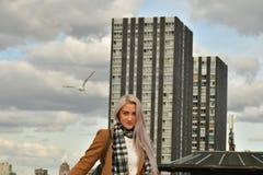 Blonde en capa en el tejado del rascacielos fotografía de archivo
