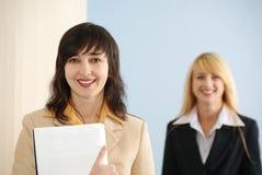 Blonde en donkerbruine vrouwen in bureau Royalty-vrije Stock Afbeeldingen