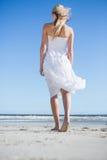 Blonde en el vestido blanco que da un paseo en la playa Imagen de archivo