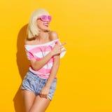 Blonde en gafas de sol rosadas que señala en el espacio de la copia Imagen de archivo