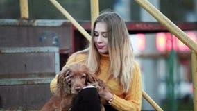 Blonde en hond de cocker-spaniël die zij heeft gestreken, raakt omhelzingenkussen verheugt zich glimlachen in de avond stad stock footage