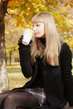 Blonde en la consumición negra de la taza Imagen de archivo libre de regalías
