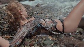 Blonde en un bikini y una túnica que descansan en el mar y almacen de video