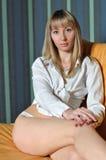 Blonde en un sofá en una camisa blanca y pantalones Imagen de archivo